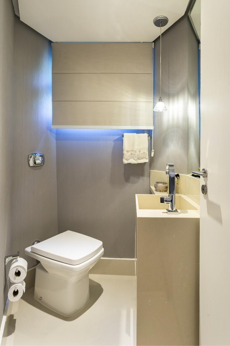 Neste banheiro de material Crema Prime Industrializado,otimizamos espaço ao usarmos a pedra do lavabo para um compartimento de toalhas e pequenas prateleiras.