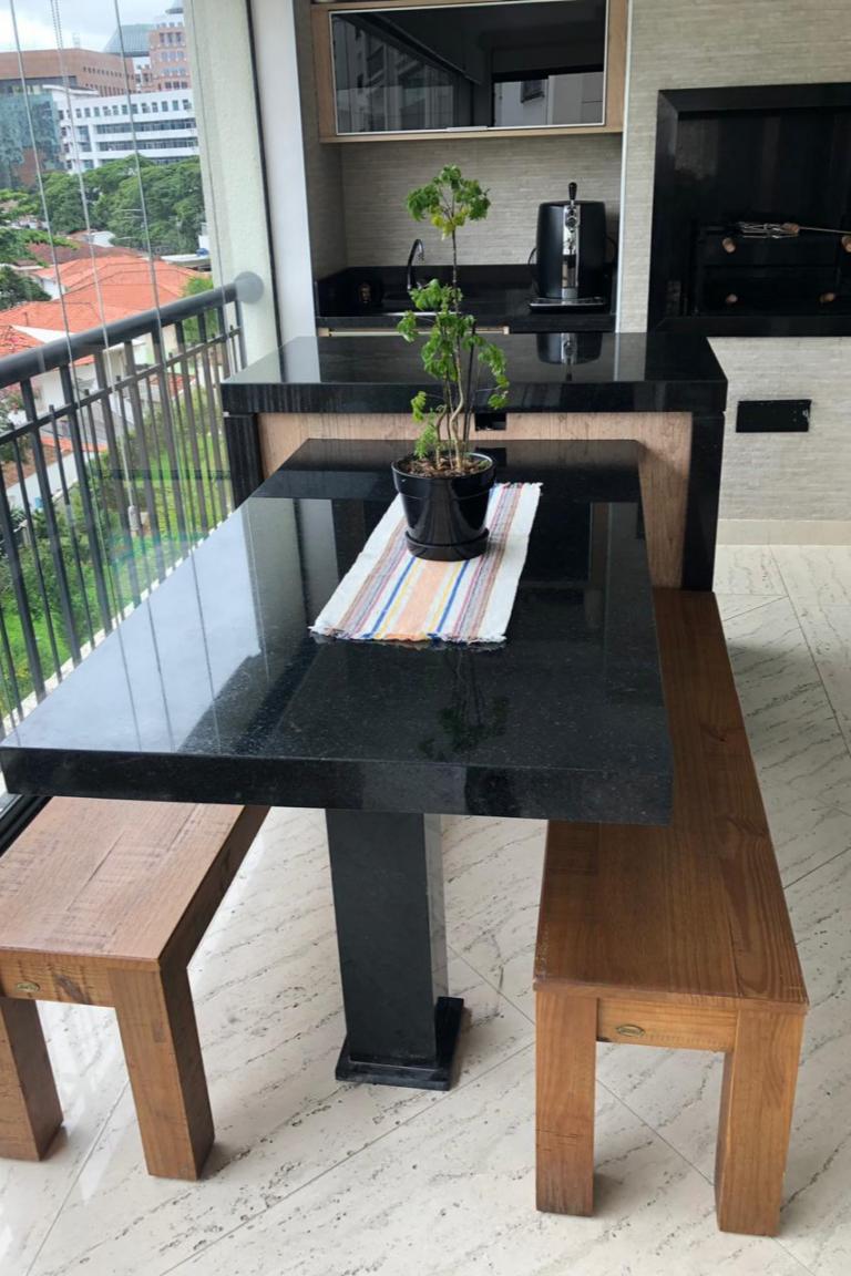 Área gourmet, com uma mesa em granito preto São Gabriel